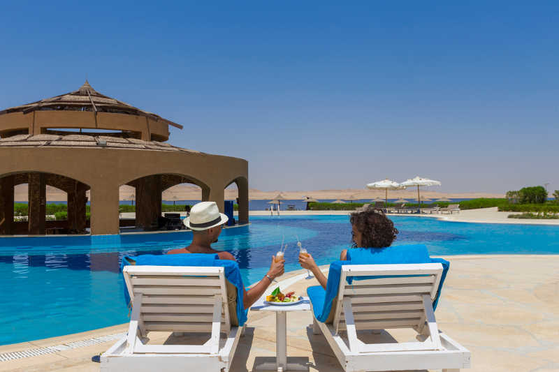 couple having a drink by the pool with a lake view at byoum lakeside hotel in fayoum