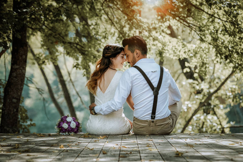 couple surrounded by green plants on their wedding day